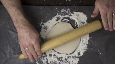 Roll the dough with a rolling pin for a home pizza. Video Live Action