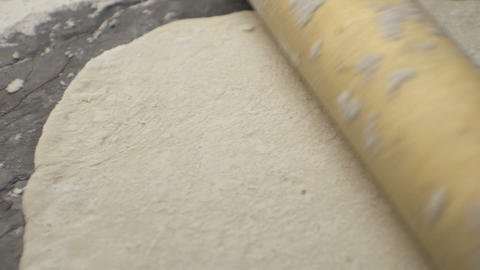 Wooden rolling pin and a rolled dough on the table. Video Live Action