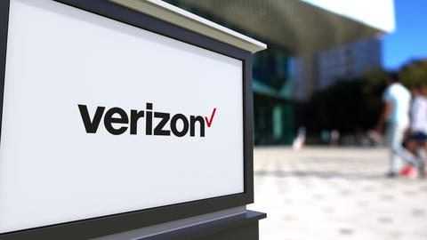 Street signage board with Verizon Communications logo. Blurred office center and Footage