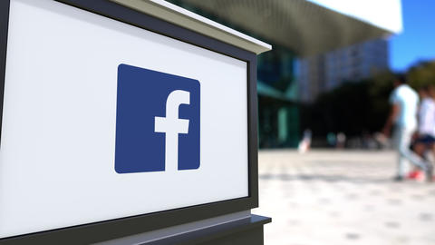Street signage board with Facebook logo. Blurred office center and walking Live Action