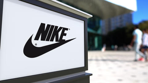 Street signage board with Nike inscription and logo. Blurred office center and Footage