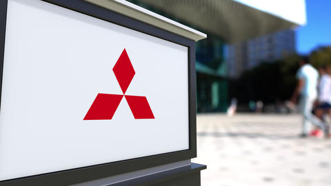 Street signage board with Mitsubishi logo. Blurred office center and walking Footage
