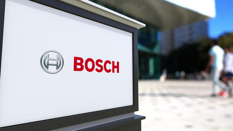 Street signage board with Robert Bosch GmbH logo. Blurred office center and Live Action