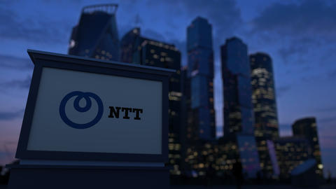 Street signage board with Nippon Telegraph and Telephone Corporation NTT logo Live Action