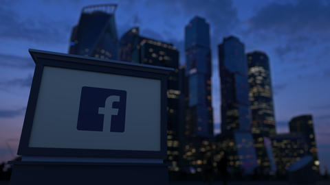 Street signage board with Facebook logo in the evening. Blurred business Live Action