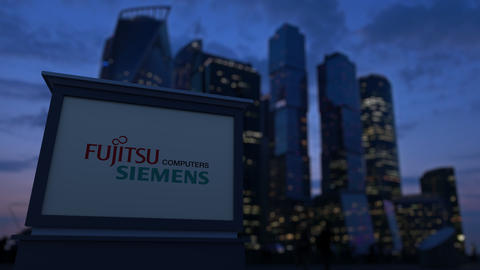 Street signage board with Fujitsu Siemens Computers logo in the evening. Blurred Footage