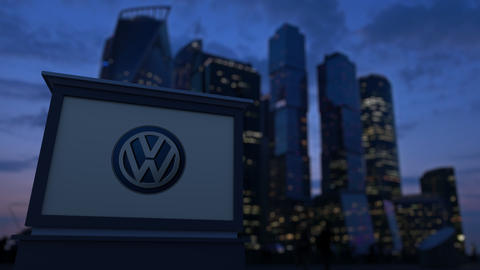 Street signage board with Volkswagen logo in the evening. Blurred business Footage