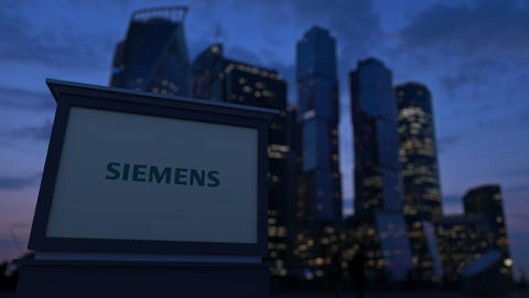 Street signage board with Siemens logo in the evening. Blurred business district Footage