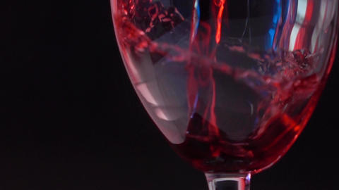 Pouring red wine into glass against black background with French flag-like Footage