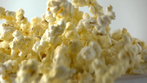 Pouring fresh popcorn into paper box. Cinema, overflow or fast food concepts Footage