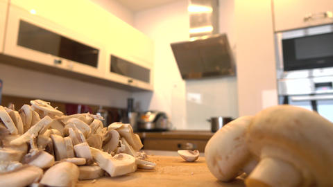 Man slicing field mushrooms in the kitchen Footage