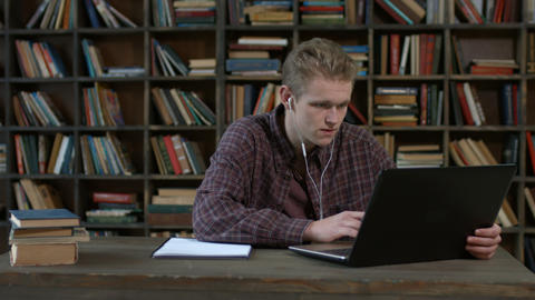 Handsome student with laptop e learning at home Footage