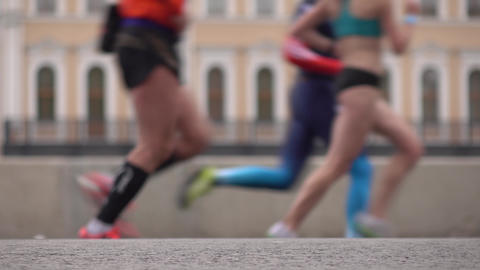 Defocused city marathon runners. Legs closeup. Competition concept. 4K long shot Footage