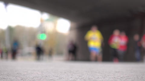 Blurred city marathon runners running under the bridge. Competition concept. 4K Footage