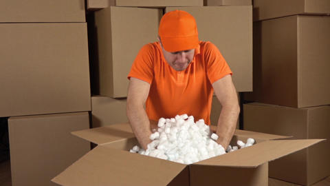 Warehouse worker in orange uniform unboxing big carton full of soft packaging Footage