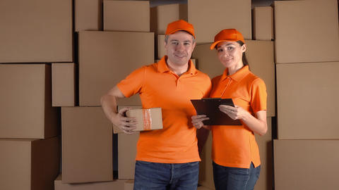Couriers in orange uniform standing against brown carton stacks backround Footage