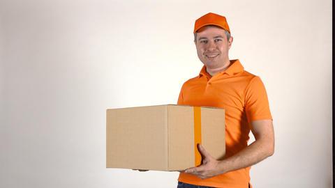 Delivery man in orange uniform delivering a big box. Light gray backround, 4K Footage