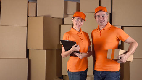 Male anf female couriers in orange uniform standing against brown cardboard Footage