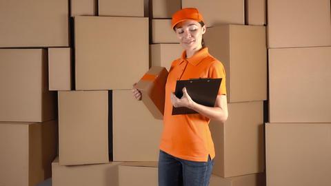 Slender girl in orange uniform delivering a parcel against carton stacks Footage