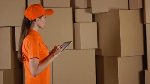 Female warehouse worker in orange uniform counting boxes and using her tablet Footage