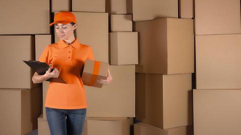 Pretty female courier in orange uniform delivering a parcel against cardboard Live Action