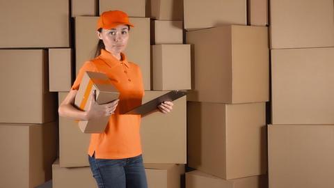 Beautiful female courier in orange uniform delivering a parcel against carton Footage