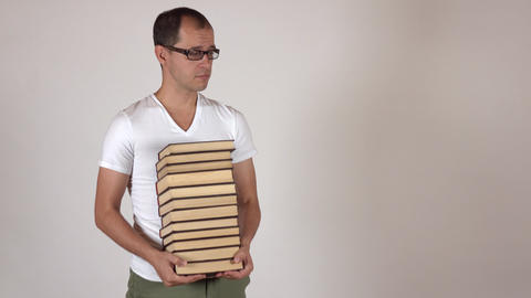 Nerdy man in black rim glasses carrying big stack of books against gray Live Action