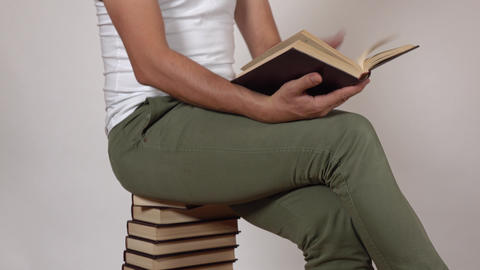 Man in green pants reads a book sitting on a big stack of books. Gray background Footage