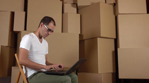 Programmer of a small online shop at work. Man in glasses working on his laptop Footage