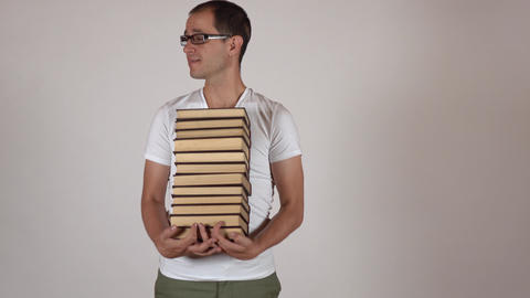 Funny nerdy man in black rim glasses carrying big stack of books against gray Footage