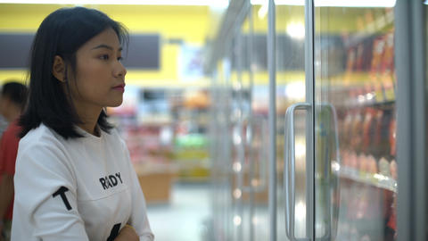 Girl taking pack of sausages out from fridge in hypermarket Footage
