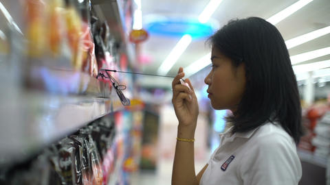 Asian Girl is trying perfume tester in a household department Footage