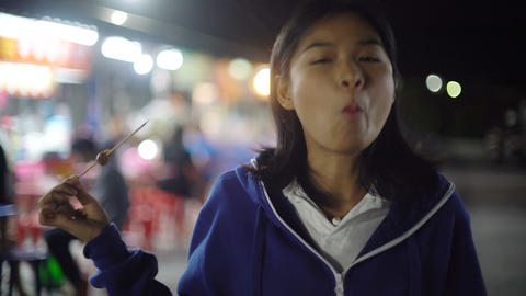 Young woman eating barbeque on skewers in night food market Footage