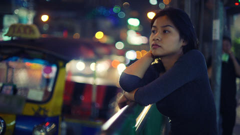 Young Asian Woman stands on street of night city Footage