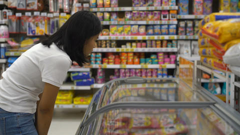 Woman choosing semi finished products in freezer at grocery Footage
