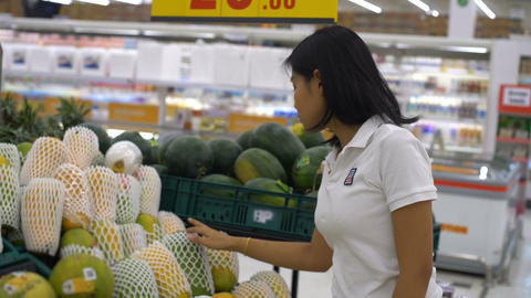 Young Asian Woman is buying papaya in a supermarket Footage