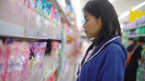 Asian girl is choosing household chemicals in supermarket Live Action