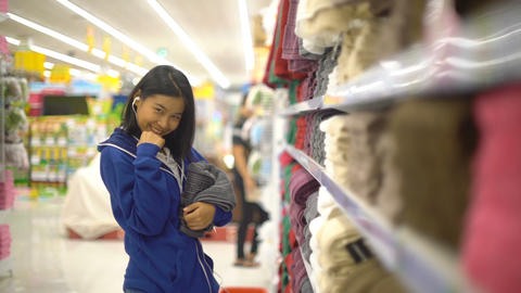 Happy Asian Woman is buying towel in supermarket Footage
