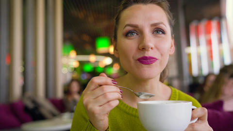 Woman drinking coffee with whipped cream, chocolate syrup with a spoon in a cafe Footage