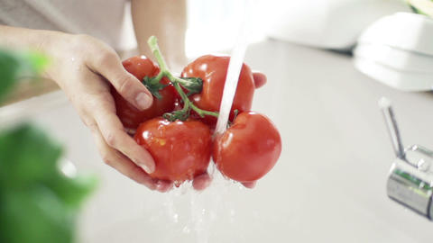 Woman washing tomatoes under tap water slow motion ビデオ