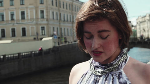Troubled young woman in spotted dress sings at riverside in old city centre Footage