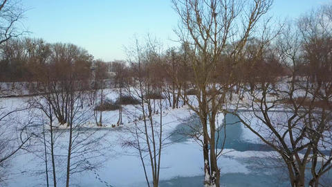 Aerial view of a winter frozen river surrounded by trees and banks covered with ビデオ