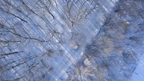 Aerial view on car driving through winter forest road. Scenic winter landscape Footage