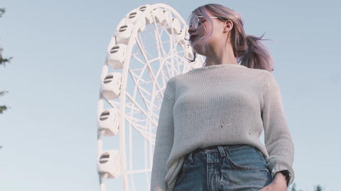 Pretty young girl in glasses standing under ferris wheel in amusment park Footage