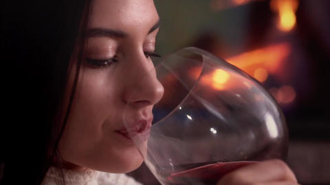 Young woman sitting at home by the fireplace and drinking a red wine Footage
