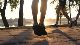 Close up of feet jumping with a skipping rope and couple of runners behind Footage