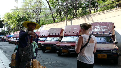 Guy passing by smiling and selling bamboo money boxes while a tourist passing by Footage