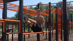 Topless athlete performing abdominal exercises on the parallel bars. 50 fps Footage