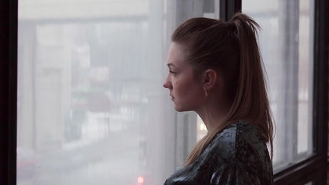 Unhappy young woman looks out the window Footage