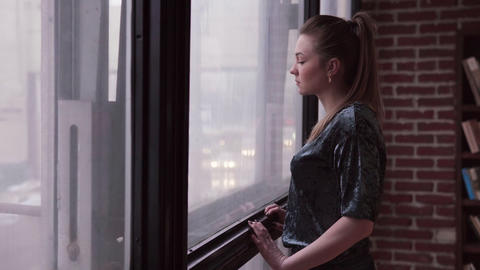 Sad woman looks at the city street outside the window Footage